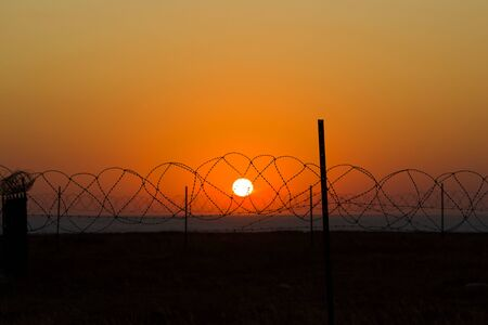 silhouette of barbed wire against the setting sun. freedom concept. Standard-Bild
