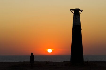 girl and a lighthouse against the backdrop of the sunset. silhouettes and contour landscape. Standard-Bild