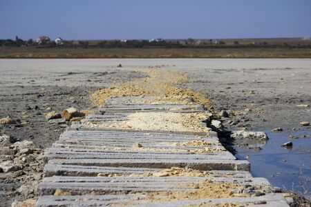 dried salty lake and wooden walkways going from the shore. Standard-Bild