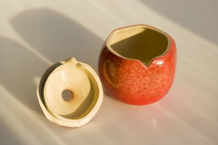 red ceramic pomegranate. vase, casket, decor, art object for the interior. pomegranate - a symbol of health, fertility and family. with cover