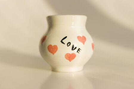 small white pot with hearts and the inscription Love. ceramic product. author's work.