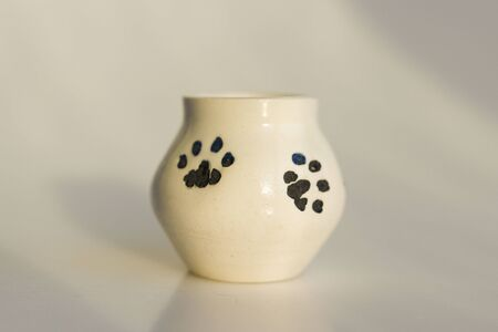 small white potty with cat's legs. prints of cat's paws. ceramic product. author's work.