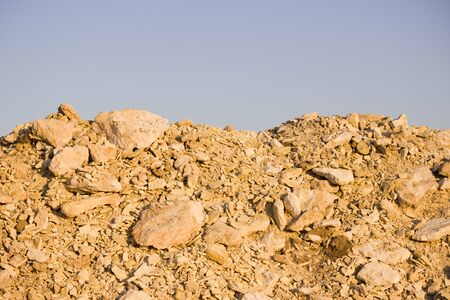 limestone and gravel mining for the construction of a road in the steppe. Pit dug by the excavator near to the future road and sea.