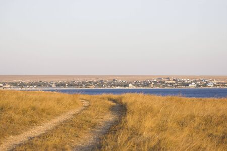 the road to the sea runs along the steppe with a feather grass. sea, seaside town and sky on the horizon. Banque d'images - 143346724