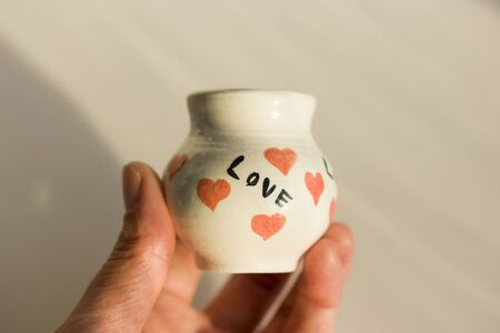 small white pot with hearts and the inscription Love. ceramic product. author's work. Standard-Bild - 143348903