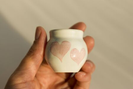 small white pot with two hearts. concept love. ceramic product. author's work Banque d'images