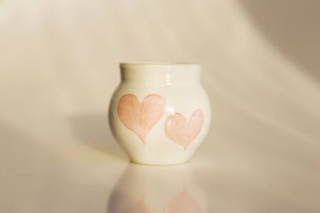 small white pot with two hearts. concept love. ceramic product. author's work Standard-Bild - 143348883