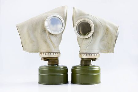 two old soviet gas masks on a white background. concept of peace and war. a means of protection against chemical and virological weapons.