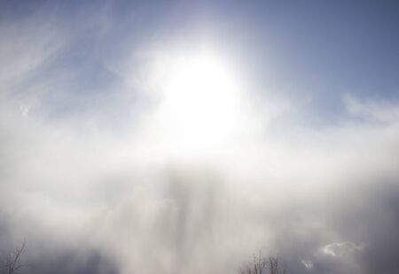 cloudy sun with a crawling snow cloud on sky. element of nature. milk light. Standard-Bild - 143458361
