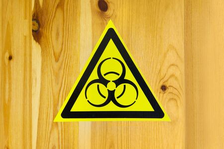 sign of biological danger and biological weapons for warning inscriptions. sticker on wooden background.
