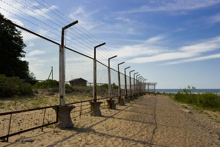 high mesh fence and barbed wire around the protected area