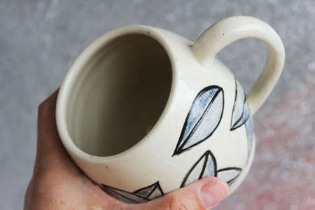 handmade ceramic cup with leaves. clay covered with engob, glaze and passed two firing.