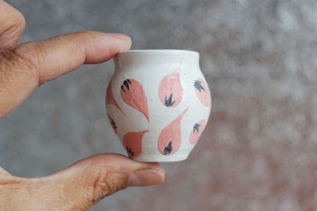 small handmade white clay pot for making wishes or flowers from boutonnieres. Decor engobe, covered with transparent glaze, two firing