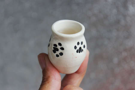 small handmade white clay with cat paws pot for making wishes or flowers from boutonnieres. Decor engobe, covered with transparent glaze, two firing Standard-Bild