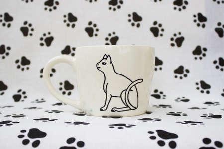 white clay mug with the Egyptian hieroglyph Cat. Handmade. Decor engobe, covered with transparent glaze, two firing Standard-Bild
