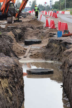 repair work to widen the road. A long ditch filled with sewage with concrete rainwater and excavators in the background.