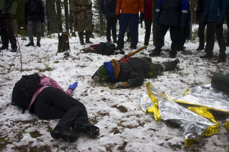 Ambulance drills in the winter forest. Several allegedly drunk people lie with knives and axes in their backs and resist helping. Reportage shooting from the scene