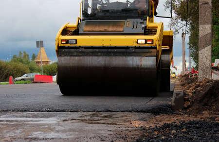 road roller compactor at work. asphalt pavement works for road repairing. expansion and repair of the roadway at the exit from the city of Gatchina, Russia Standard-Bild