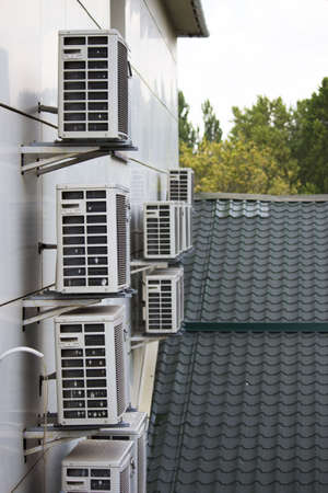 group of old outdoor air conditioner units on the facade of the house