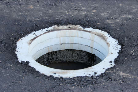 concrete ring from a storm drain on an asphalt road. road repair and widening, reportage photo Standard-Bild