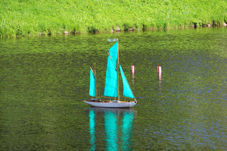 small turquoise sailboat on the lake, controlled remotely