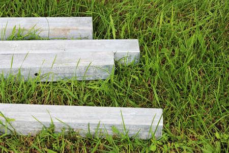 four concrete blocks lie on the grass. blanks for pillars