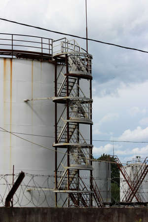 huge industrial tank with a metal ladder against the blue sky Standard-Bild