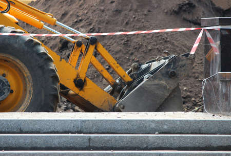 tractor with a bucket works behind a protective protective tape of red and white color. construction and repair work of the road