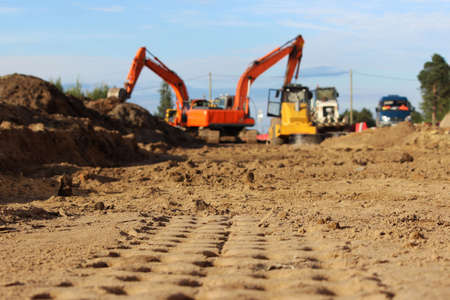 imprints of traces of heavy equipment in the sand. working excavators in the background. repair and construction of a road in the city