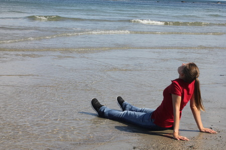 head back: Woman in Red Shirt Sitting on Beach in Water with her head back fully dressed.
