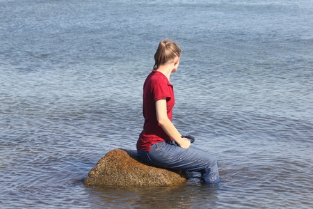 Woman Fully Dressed Sitting on Rock in the Ocean. Stock Photo