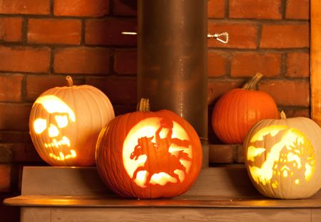 halloween carved pumkins sitting on the wood stove photo