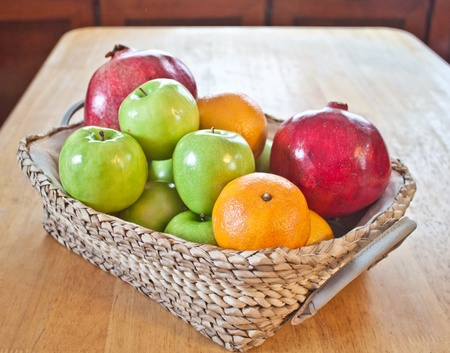 fruit basket on the table with apples, oranges and pomegranates Stock Photo - 8355100