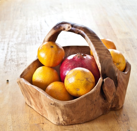 Fuit in a hand carved wooden basket on the table Stock Photo - 8355094