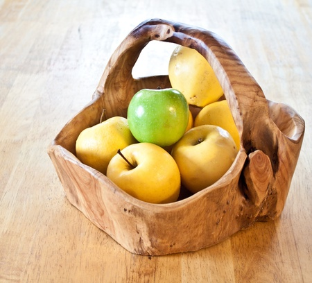 all yellow apples and one green one in a hand carved wooden basket Stock Photo - 8397867