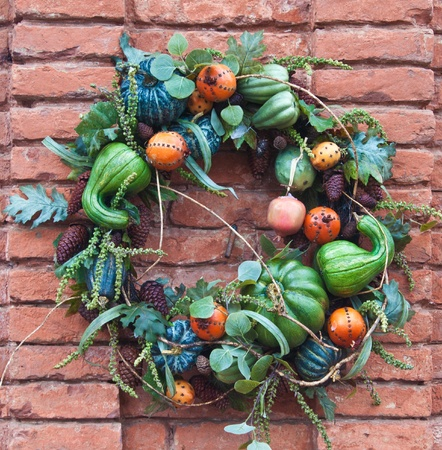 decorration: brick wall decorated for autumn with gords in a wreath, in california mid december