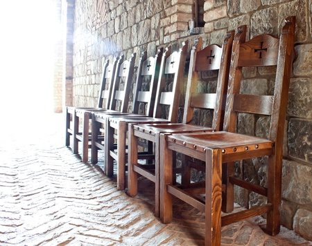believes: A row of chair lined up against the wall tith religios simbols on them and a bright back light