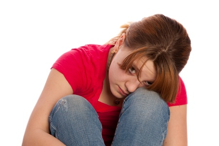 atractive: young girl in her teenager years meditating and showing signs of being sad or thinking a lot Stock Photo