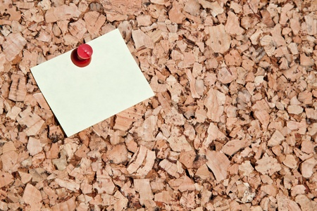 pin board: blank sticky note stuck on a cork board with a red pin