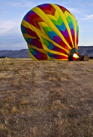 inflating a hot air ballon in an open field photo