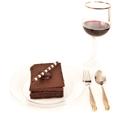 prety: chocolate brownie on a white table with a glass of red wine in the background isolated on white