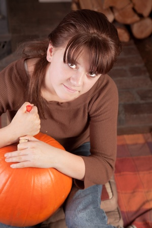 prety: young girl sitting down concentrated carving a pumpking for halloween Stock Photo