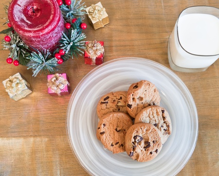 chritmas: Chocolate chip cookies and milk as a center piece for a chritmas scene on a golden place mat Stock Photo