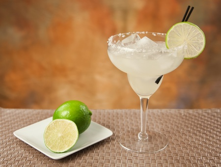 alcoholic drink: fresh margarita with limes on a plate and salt rim