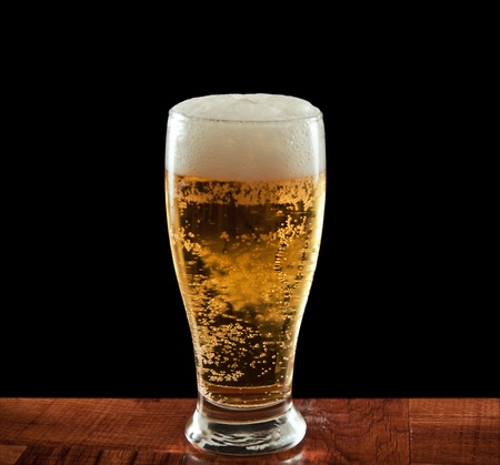 Glass of beer on a wooden bar isolated on a black backgound photo