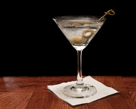 Martini on a bar garnished with bleu cheese olives isolated on a black background