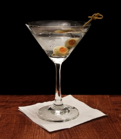 gin: Martini on a bar garnished with a lemon twist isolated on a black background Stock Photo