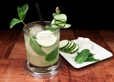 old fashioned vegetables: alcoholic beverage on a bar top with cucumber slices, mint and sugar cubes on a plate