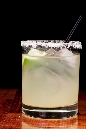 close up of a margarita garnished with a freh lime and a salt rim around the glass