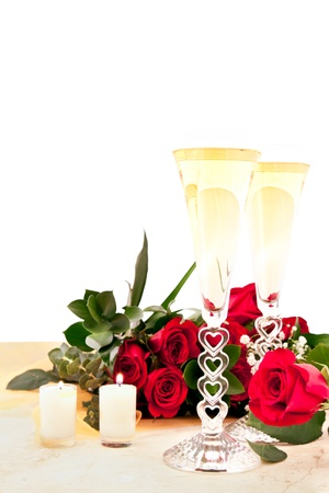 newyears: red roses and champagne on a slate countertop with two candles lit for valentines